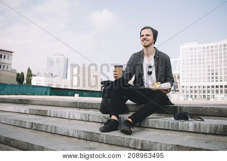 The traveller is sitting on white stairs. He is holding a plate with his snack in one hand. The other one is holding a cup of hot coffee. On the right from him we can see his black backpack. On the left side there is a camera.