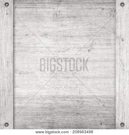 Side of white wooden crate, box, or frame with screws.