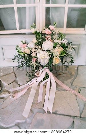 Rustic wedding bouquet with creamy roses, white carnations, and eustoma stand on the floor. Close-up. Side view Indoors.
