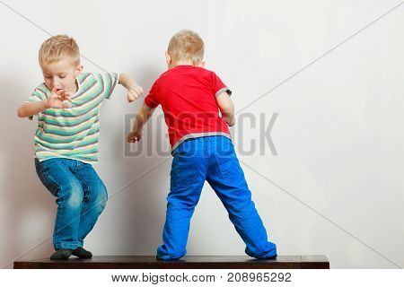 Childhood relationship between brothers concept. Two little boys siblings playing together on table having fun.