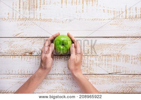 Young Woman Hands Holding Ripe Green Apple on White Plank Wood Background Tabletop. Flat Lay Top View Thanksgiving Harvest Autumn Fall. Gratefulness. Copy Space. Creative Conceptual Image