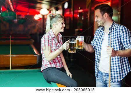Couple drinking beer playing snooker on date together