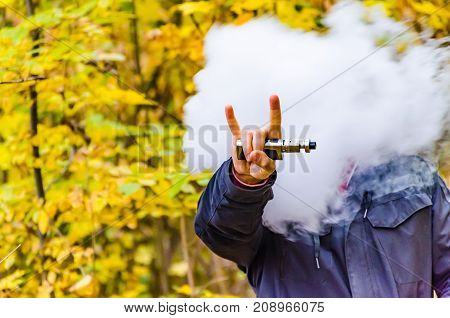 Young Man Smoking And Electronic Ciggarette