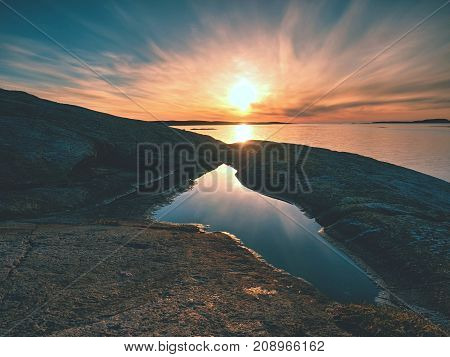 Beautiful Seascape. Mirroring Of  Sunset In Water Pools In The Rocks . Smooth Ocean