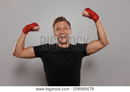 Young excited sportsman with hands in red band posing victoriously on gray background looking at camera.