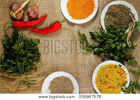 assorted spices pepper ground paprika hop schili and garlic and parsley on burlap. View from above