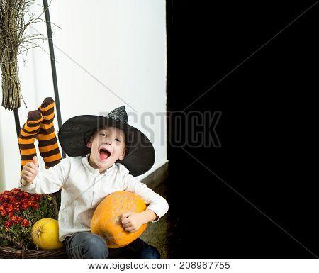 Halloween Kid With Orange Pumpkin In Witch Hat