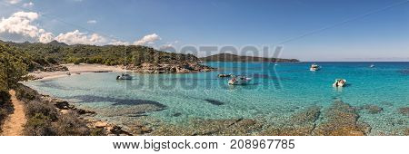 Boats In A Small Rocky Cove With Sandy Beach In Corsica