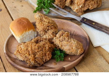 Fried chicken and dinner roll on a wooden plate