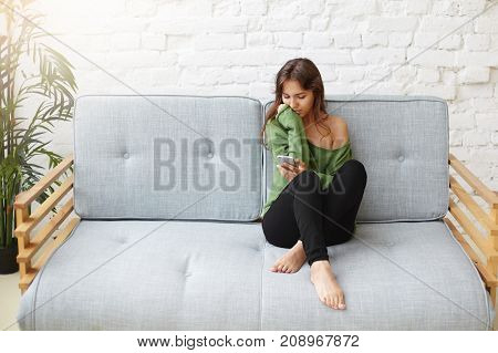 Stunning barefooted young Latin female wearing oversized off shoulder green sweater messaging friends online on cell phone inviting them to party relaxing on sofa with copy space for your content