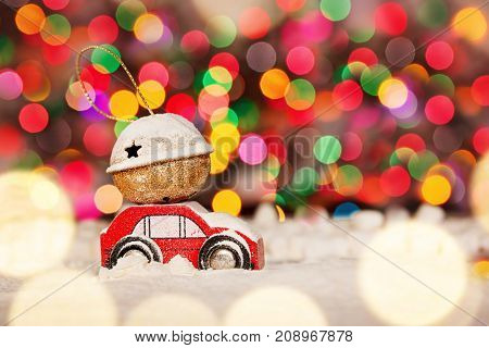 Miniature Red Car Carrying a Gift on colorful bokeh background. Holiday Merry Christmas concept.