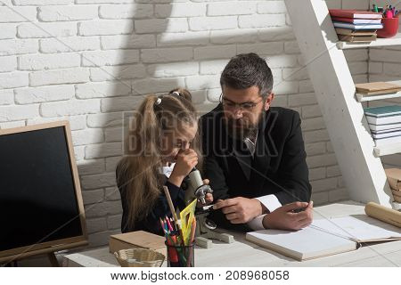 Girl and man sit at desk and look into microscope. Home schooling and back to school concept. Kid and tutor with attentive faces. Teacher and schoolgirl in study or lab room on white brick background