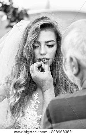 young sexy woman with long blonde hair and pretty face in wedding white dress and bride blue veil making makeup with male hand