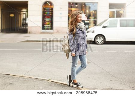 Street fashion and urban style concept. Outdoor lifestyle portrait of beautiful fashionable young female wearing stylish clothes and accessories waiting for taxi or friend on corner of street