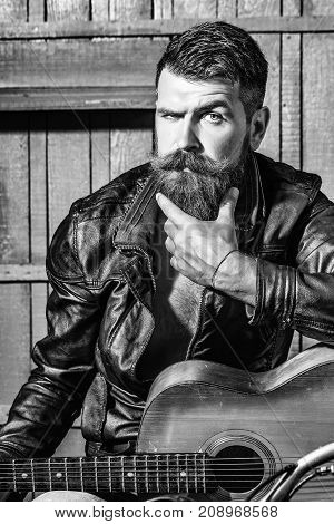 Frown bearded man hipster biker brutal male with beard and moustache in leather jacket sits on motorcycle with guitar on wooden background