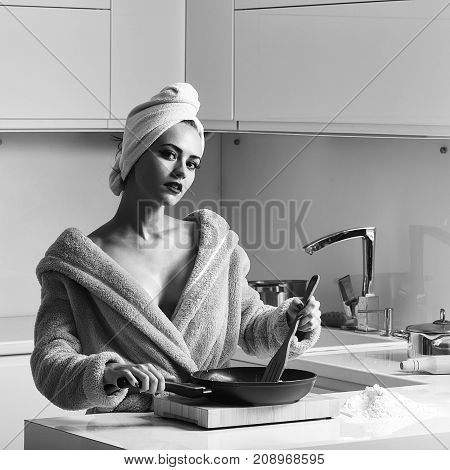 One sexual beautiful sensual female housewife in blue terry dressing gown and towel turban on head with bare shoulders standing in kitchen cooking breakfast from fried eggs in morning life square