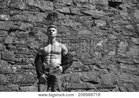 Man bare-chested young pose sexy model in jeans outdoor on mural background