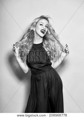 Attractive sexy woman with blonde curly hair posing in black elegant dress in studio on yellow background