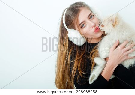 New year of dog and winter holiday celebration. Xmas party and vacation. Dog in hand of woman on white background. Girl with happy face in gloves and ears. Woman with small dog of Pomeranian Spitz.
