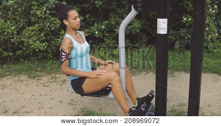 Confident young girl in sportswear training in park sitting on exerciser and listening to music looking forward on background of green trees.
