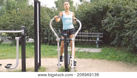 Confident young woman in sportive clothing working out on exerciser in street gym while listening to music with smartphone and looking away.