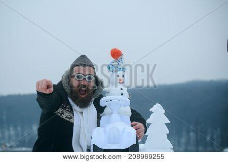 Bearded Hipster Pointing Finger On Winter Landscape
