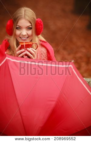 Happiness carefree and fall concept. Joyful woman relaxing in autumn park on bench under umbrella enjoying hot drink holding mug with warm beverage. Orange leaves background