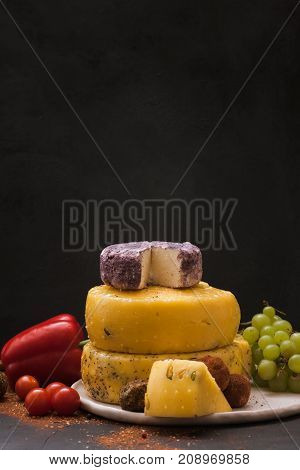 Gourmet sorts of cheese with variety of vegetables, fruits and spices on black background. Assortment composition of luxury products, close up, free space. Rustic local dairy advertisement