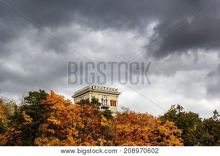 A tall building with a clock against an approaching storm in the sky. An ancient building among the foliage and the approaching thunderstorm