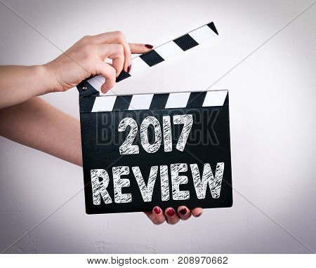 2017 review. Female hands holding movie clapper.