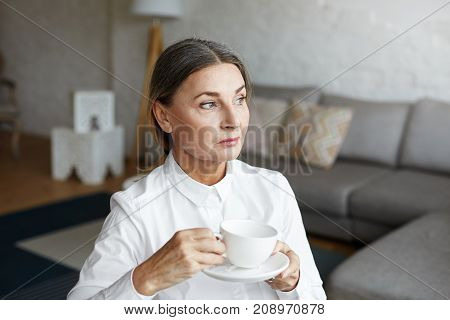 Indoor shot of beautiful serious middle aged university professor in white blouse relaxing at her study after lecture ejoying coffee or tea sitting in modern interior with grey sofa in background