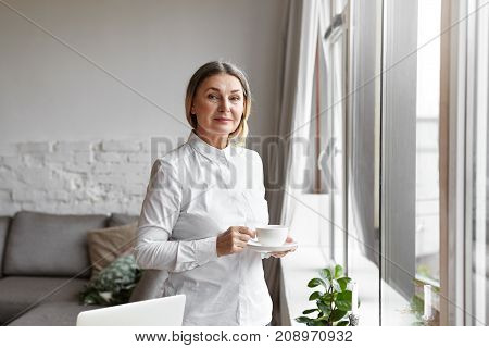 Attractive confident middle aged woman family counselor wearing white shirt having coffee break standing with mug by the window at office waiting for her clients. People job and occupation concept