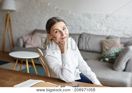 Picture of beautiful middle aged female history teacher with gathered hair sitting at desk at home or office with grey couch in background preparing for lesson or checking copybooks of her students
