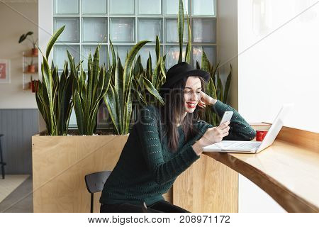 Stylish young female fashion blogger in round hat sitting at cafe by the window and working on content for her blog using generic laptop and reading text message on mobile waiting for her coffee