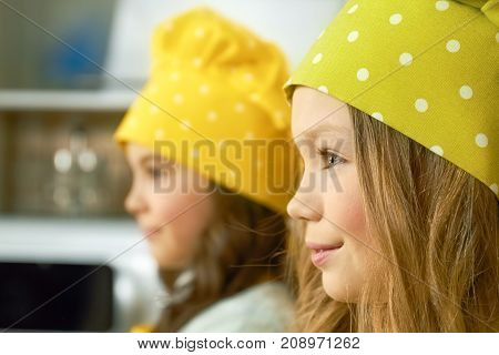Little girl face side view. Child in the kitchen.