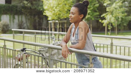 Young content model leaning on metal fence if bridge in park with bicycle standing near and looking dreamily away.