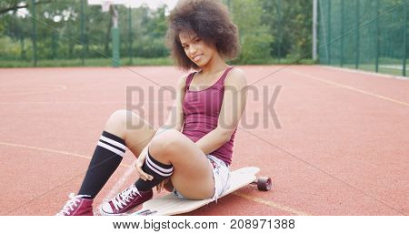 Pretty and flirty model in casual clothing sitting on longboard while looking at camera on background of basketball sports ground.