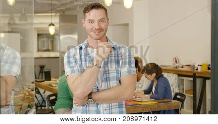 Handsome young man in casual clothing standing in modern office on background of other employees and smiling at camera.