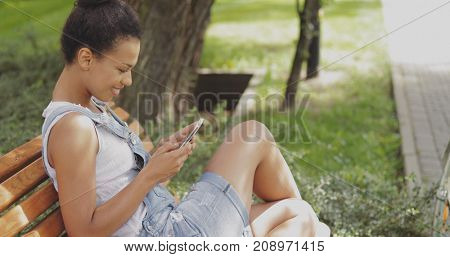 Side view of young pretty woman posing on bench in summer park and browsing smartphone smilingly in morning time.