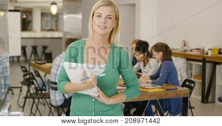 Casual woman posing with heap of documents in hands and looking at camera on background of people in office.