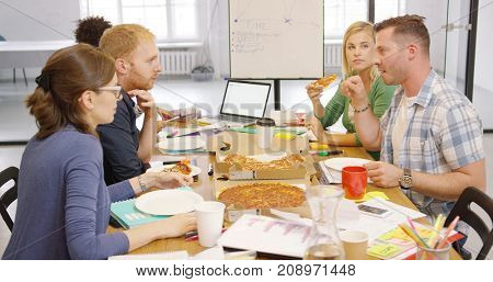Side view of friendly colleagues relaxing at table in office having ordered pizza and talking lively while resting.