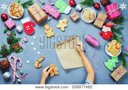Christmas background with gifts cookies Christmas decoration and children's hands writing a letter to Santa Claus