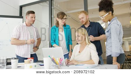 Multiracial group of young people gathering around table in modern office and watching laptop all together communicating and discussing new ideas.