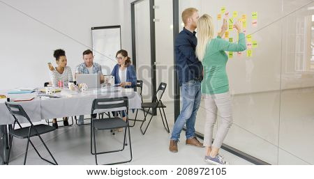 Group of people in modern office and two of them brainstorming on new plan using stickers and building diagram on glass wall.