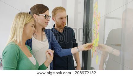 Side view of two women and male coworker creating new ideas on project and putting stickers on glass wall of office.