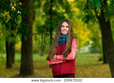 Closeup Portrait of young girl with long hair in the autumn park on the background of yellow leaves. woman autumn portrait
