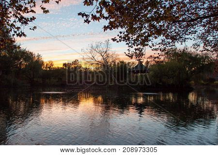 An orange glowing sunset over a park like setting of a calm pond with a bridge and gazebo and fall trees.