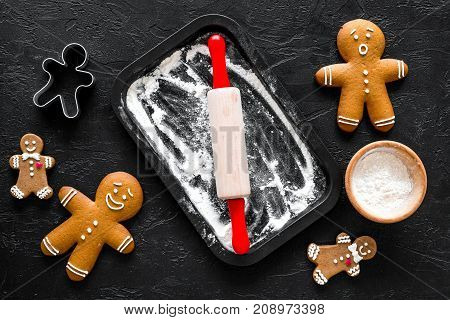 Cook gingerbread for new year 2018. Gingerbread man, rolling pin, flour on black background top view.