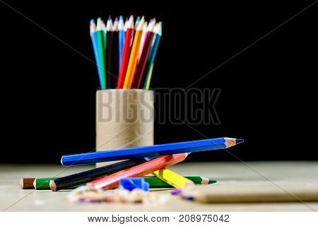Crayons And Pencil Sharpener On A Wooden Office Table. Crayons With Sharpening Crayons And Pencils O