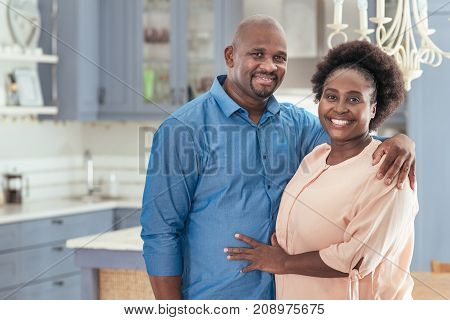 Portrait of a smiling African couple affectionately standing together in their kitchen at home